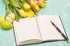 Easter eggs, blank daily log and tulips. Stock Photo