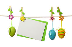 Easter eggs and blank note. Hanging on the clothesline isolated on white background royalty free stock images