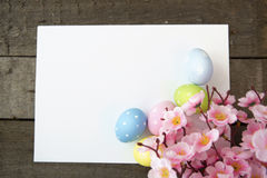 Easter eggs and blank note on wooden background Stock Photo