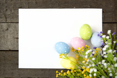 Easter eggs and blank note on wooden background Stock Photography
