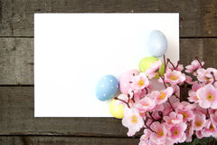 Easter eggs and blank note on wooden background Stock Photos