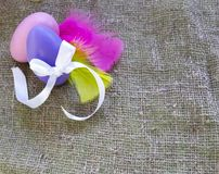 Easter eggs with bow knot and colored feathers  on burlap background stock photography