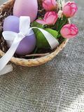 Colorful eggs with bowknot and roses in basket on burlap background. Easter eggs with bowknot and decorative roses in basket on burlap surface. Place for text royalty free stock images