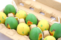 Easter eggs in a box. Green and yellow easter eggs in a box stock image
