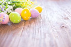 Easter eggs and branch with flowers on rustic wooden background. Stock Image