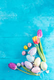 Easter eggs on bright blue background. Easter eggs ans tulips on bright blue background Royalty Free Stock Images