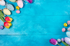 Easter eggs on bright blue background. Easter eggs and tulips top view frame on bright blue background Stock Photo