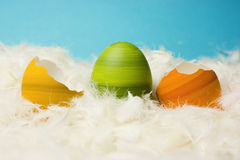 Easter eggs broken. Broken green, orange and yellow easter eggs, hand-painted, lying in white feathers, blue background Stock Photos