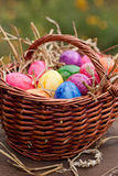 Easter eggs in a brown basket Stock Images