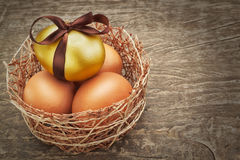 Easter eggs with brown ribbon in a nest. Easter eggs with brown ribbon in a nest on a wooden texture royalty free stock photo