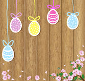 Easter eggs on a brown wooden background with flowering branches. Painted colored Easter eggs on a wooden background with flowers Stock Image