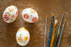 Easter eggs and brushes. On wooden background Royalty Free Stock Image