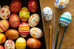 Easter eggs and brushes. On wooden background Royalty Free Stock Photos