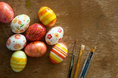 Easter eggs and brushes. On wooden background Stock Photos