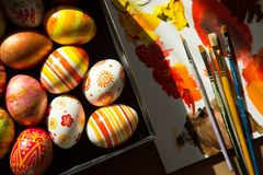 Easter eggs, brushes and paints. On wooden background Stock Image