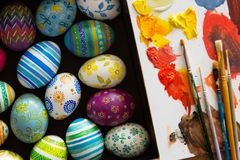 Easter eggs, brushes and paints. On wooden background Royalty Free Stock Images