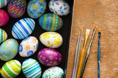 Easter eggs and brushes. On wooden background Royalty Free Stock Images