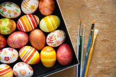 Easter eggs and brushes. On wooden background Stock Photo