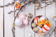 Easter eggs in bucket, decorative rabbit  and willow  branches o Royalty Free Stock Image