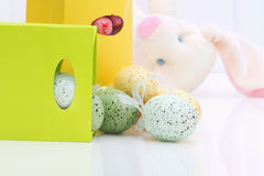 Easter Eggs and Bunny. Beautiful Easter eggs spilling from a giftbag. Cute bunny in the background. Shallow DOF Royalty Free Stock Photo