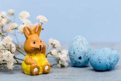 Easter background with eggs and a easter bunny and white flowers on blue paper. Easter eggs and bunny on blue wooden table and white flowers Stock Photos