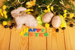 Easter eggs, bunny, dragees, flowers, butterfly and words HAPPY Stock Photos
