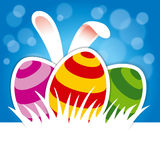 Easter eggs and bunny ears on blue background royalty free stock photography