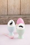 Easter eggs. With bunny  and moustache silhouettes in egg cups Stock Photos