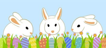 Easter eggs and bunny. Easter eggs and three rabbits in grass on blue background Stock Photo