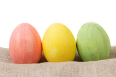 Easter eggs on burlap in a row Royalty Free Stock Photography