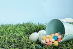 Easter Eggs and Candy Malt Eggs in Grass. Natural colored Easeter eggs and malt candy eggs spilling from a robin egg blue metal basket in the grass with room for stock images