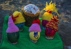 Easter eggs in caps, with funny faces in nature. Easter holiday Stock Images