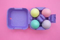 Easter eggs in carton box on bright orange background. Overhead shot of cute easter eggs stock photo