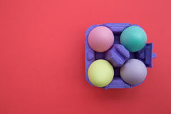Easter eggs in carton box on bright red background. Overhead shot of cute easter eggs royalty free stock photography