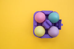 Easter eggs in carton box on yellow background. Overhead shot of cute easter eggs Stock Images