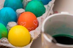 Easter Eggs in a Carton. Some Easter eggs in a carton next to some green dye Stock Photos