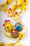 Easter eggs on ceramic plate. Chicken shape and forsythia twigs Royalty Free Stock Photo