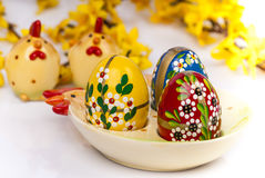 Easter eggs on ceramic plate horizontal. Easter eggs on ceramic plate chicken shape and forsythia twigs. Horizontal Royalty Free Stock Image