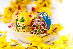 Easter eggs on ceramic plate horizontal. Easter eggs on ceramic plate chicken shape and forsythia twigs. Horizontal Stock Photo