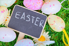 Easter eggs with chalkboard on the grass Stock Images