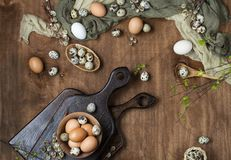 Easter eggs in chicken and quail. With willow twigs on wooden background, top view Royalty Free Stock Photo