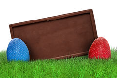 Easter eggs and chocolate bar. On grass on white background Royalty Free Stock Photo
