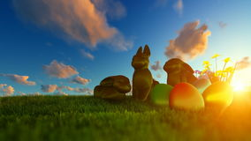 Easter Eggs and Chocolate Bunnies on green meadow against beautiful sunrise stock footage