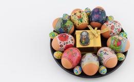 Easter eggs, chocolate bunny, and giftbox on black plate Stock Image