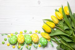 Easter eggs and tulips on wooden background. Royalty Free Stock Photo