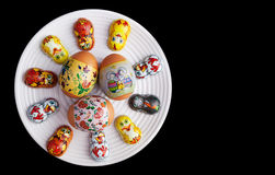 Easter eggs and chocolates on white plate Stock Photos