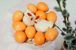 Easter eggs, cockerel and chicken figurines and willow twigs. On table Royalty Free Stock Photography