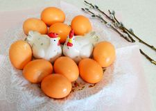 Easter eggs, cockerel and chicken figurines and willow twigs. On table Stock Photo
