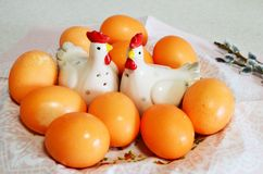 Easter eggs, cockerel and chicken figurines and willow twigs. On table Stock Image