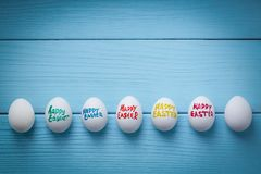 Easter eggs with color titles `Happy Easter` written by brush are on the blue colored wooden background with vignette effect.  Royalty Free Stock Images